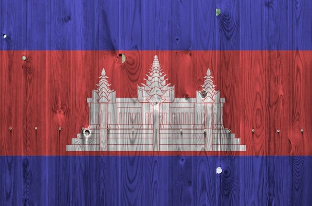 Flaga kambodży przedstawiona w jasnych kolorach farby na starej drewnianej ścianie.