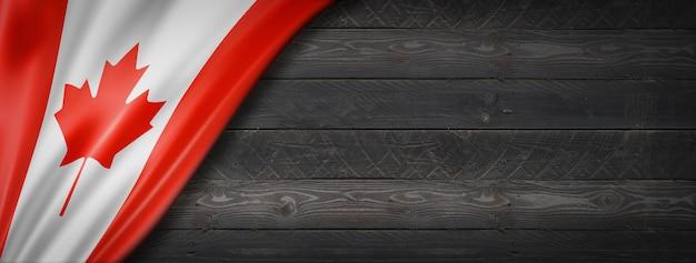 Flaga kanady na czarnej ścianie z drewna. poziomy baner panoramiczny.