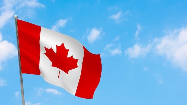 Flaga kanady na słupie. niebieskie niebo. flaga narodowa kanady