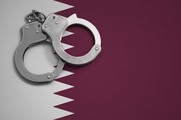 Flaga kataru i kajdanki policyjne. pojęcie przestępczości i przestępstw w kraju