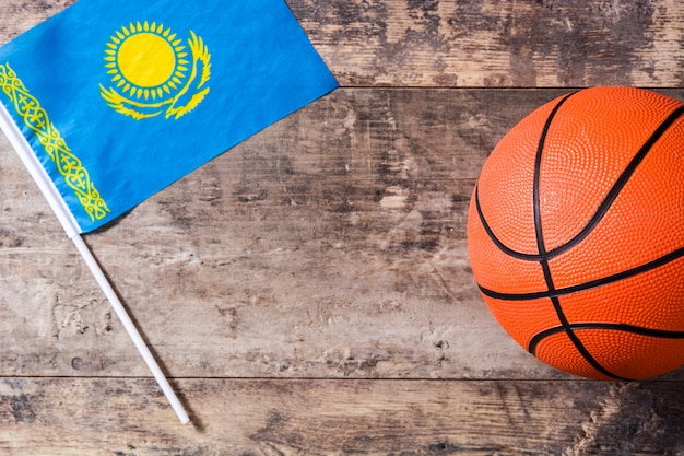 Flaga kazachstanu i koszykówka na drewnianym stole.