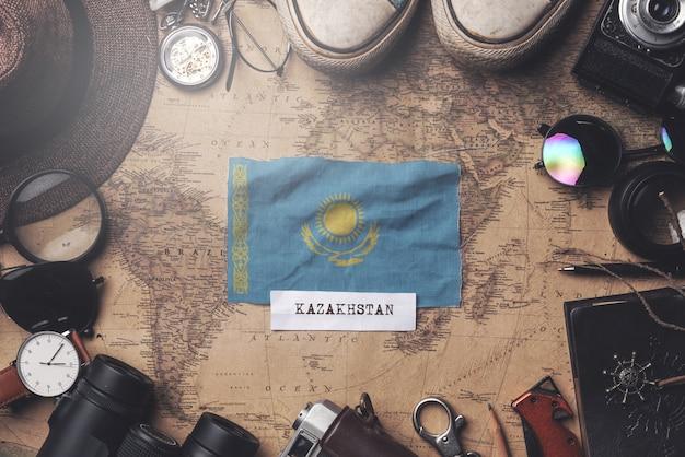 Flaga kazachstanu między akcesoriami podróżnika na starej mapie vintage. strzał z góry