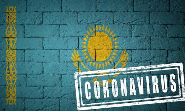 Flaga kazachstanu o oryginalnych proporcjach. opieczętowane koronawirusem. cegła ściana tekstur. koncepcja wirusa koronowego. na skraju pandemii covid-19 lub 2019-ncov.