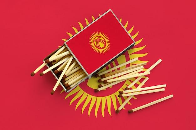 Flaga kirgistanu jest pokazana na otwartym pudełku zapałek, z którego wypada kilka zapałek i leży na dużej fladze