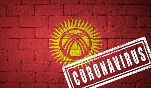 Flaga kirgistanu o oryginalnych proporcjach. opieczętowane koronawirusem. cegła ściana tekstur. koncepcja wirusa koronowego. na skraju pandemii covid-19 lub 2019-ncov.