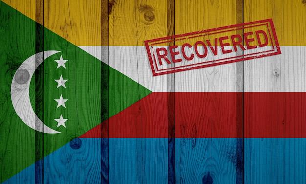 Flaga komorów, która przeżyła lub wyzdrowiała z infekcji epidemii koronawirusa lub koronawirusa. flaga grunge z pieczęcią odzyskane