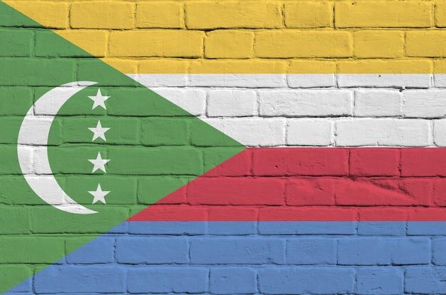 Flaga komorów przedstawiona w kolorach farb na starym murem. textured sztandar na dużym ściana z cegieł kamieniarstwa tle