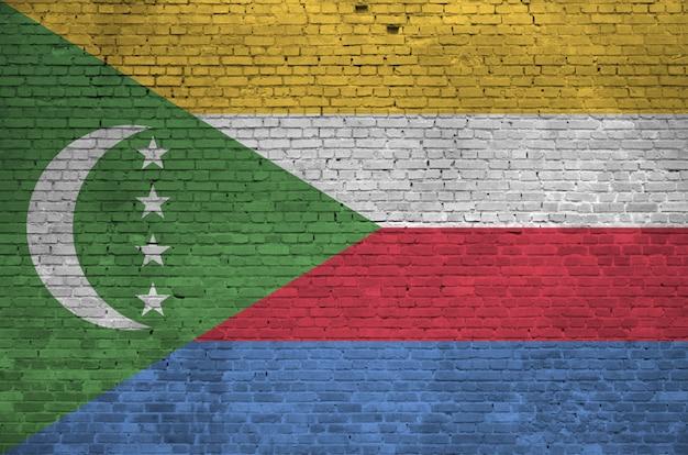 Flaga komorów przedstawiona w kolorach farb na starym murem.