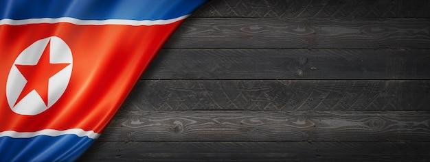 Flaga korei północnej na czarnej ścianie z drewna. poziomy baner panoramiczny.