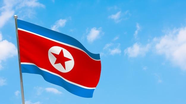 Flaga korei północnej na słupie. niebieskie niebo. flaga narodowa korei północnej