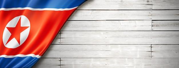 Flaga korei północnej na starej białej ścianie. poziomy baner panoramiczny.