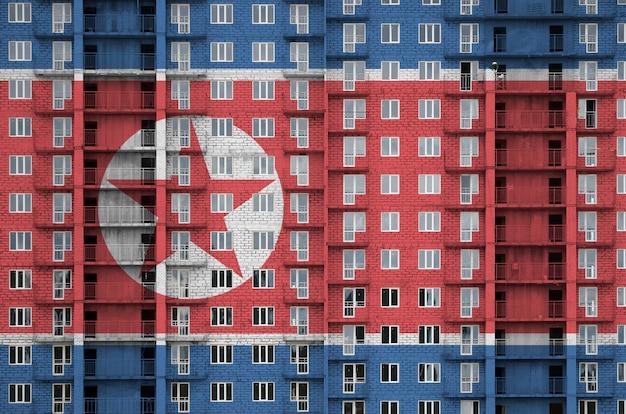 Flaga korei północnej przedstawiona w kolorach farb na wielopiętrowym budynku mieszkalnym w budowie.