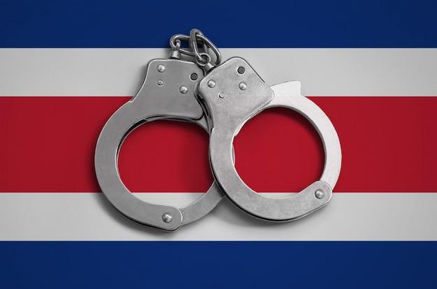 Flaga kostaryki i kajdanki policyjne. pojęcie przestrzegania prawa w kraju i ochrona przed przestępczością