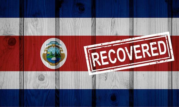 Flaga kostaryki, która przetrwała lub wyzdrowiała z zakażenia epidemią koronawirusa lub koronawirusem. flaga grunge z pieczęcią odzyskane