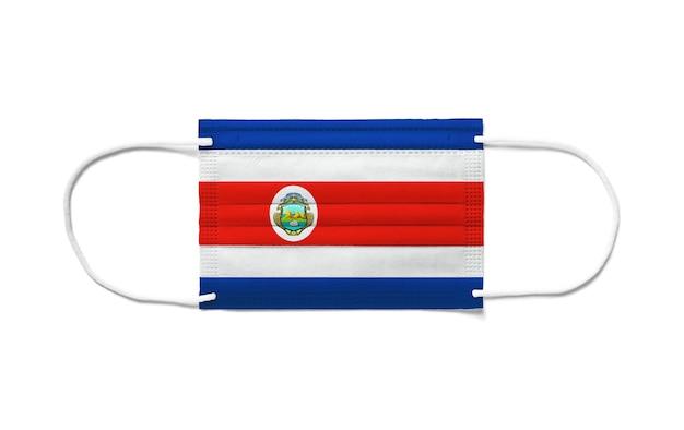 Flaga kostaryki na jednorazowej masce chirurgicznej. biała powierzchnia na białym tle