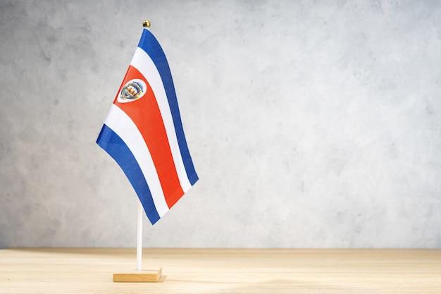 Flaga kostaryki tabeli na białej ścianie z teksturą. skopiuj miejsce na tekst, projekty lub rysunki
