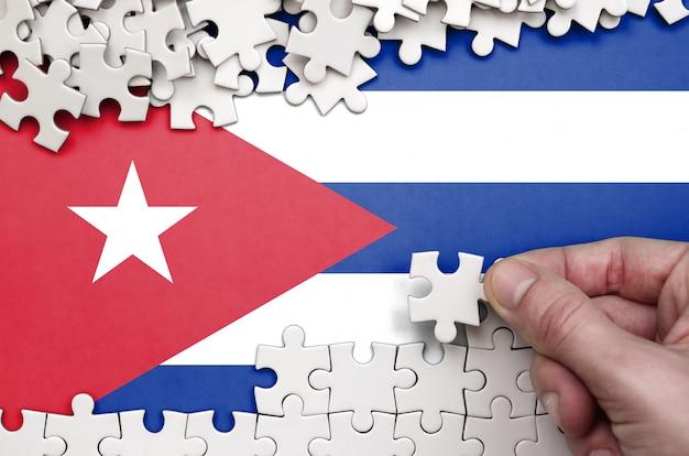Flaga kuby jest przedstawiona na stole, na którym ludzka ręka składa układankę w białym kolorze