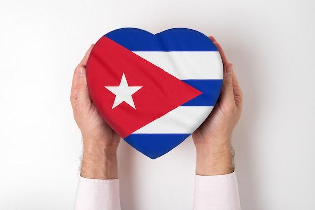 Flaga kuby na pudełku w kształcie serca w męskich rękach.