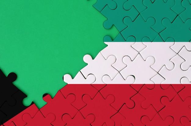 Flaga kuwejtu jest przedstawiona na ukończonej układance z bezpłatną zieloną przestrzenią po lewej stronie