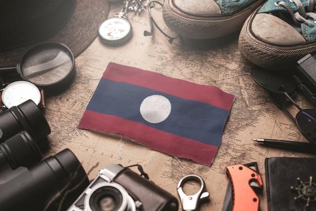 Flaga laosu między akcesoriami podróżnika na starej mapie vintage. koncepcja miejsca turystycznego.