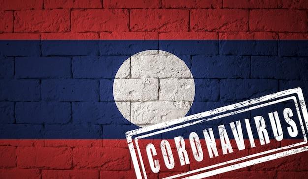 Flaga laosu o oryginalnych proporcjach. opieczętowane koronawirusem. cegła ściana tekstur. koncepcja wirusa koronowego. na skraju pandemii covid-19 lub 2019-ncov.
