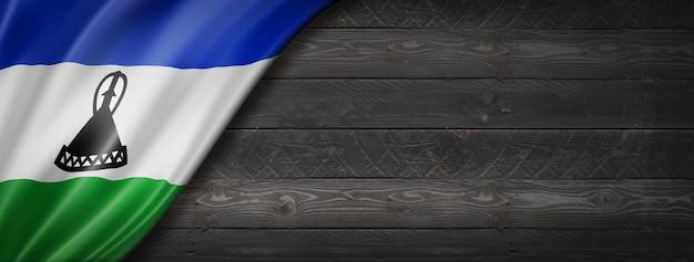 Flaga lesotho na czarnej ścianie z drewna