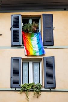 Flaga lgbt kolorów i słowa pease w języku włoskim wiszące na fasadzie budynku, bergamo