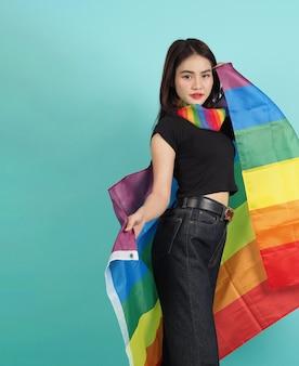 Flaga lgbtq dziewczyna i duma. seksowna dziewczyna lesbijek i stojąca flaga lgbt. niebieskie zielone tło. azjatycka kobieta lgbtq z tęczowym szalikiem na szyi. energiczny wesoły. koncepcja lgbtq.