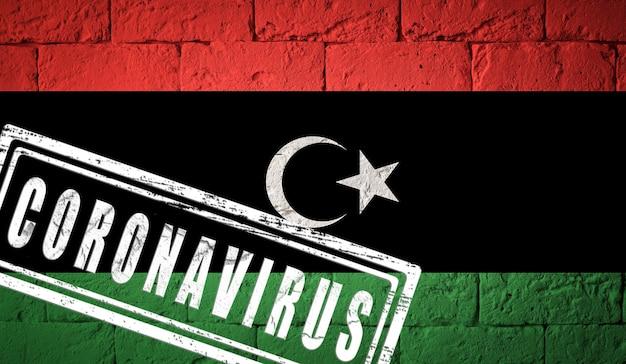 Flaga libii o oryginalnych proporcjach. opieczętowane koronawirusem. cegła ściana tekstur. koncepcja wirusa koronowego. na skraju pandemii covid-19 lub 2019-ncov.