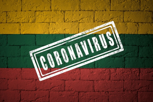 Flaga litwy o oryginalnych proporcjach. opieczętowane koronawirusem. cegła ściana tekstur. koncepcja wirusa koronowego. na skraju pandemii covid-19 lub 2019-ncov.