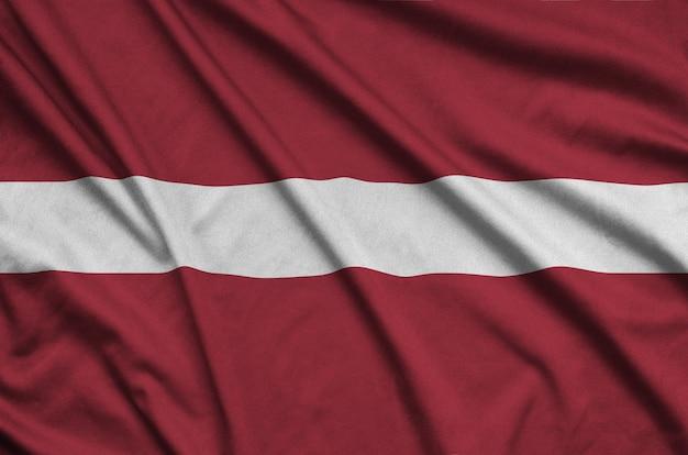 Flaga łotwy jest przedstawiona na sportowej tkaninie z wieloma zakładkami.