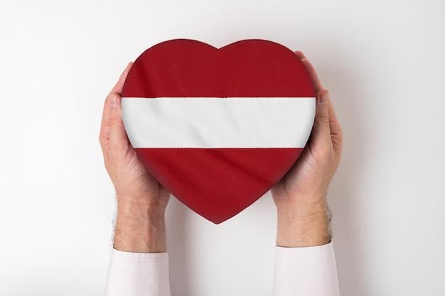 Flaga łotwy na pudełku w kształcie serca w męskie dłonie.