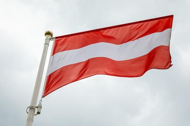 Flaga łotwy na wietrze w świetle dziennym przeciwko niebo