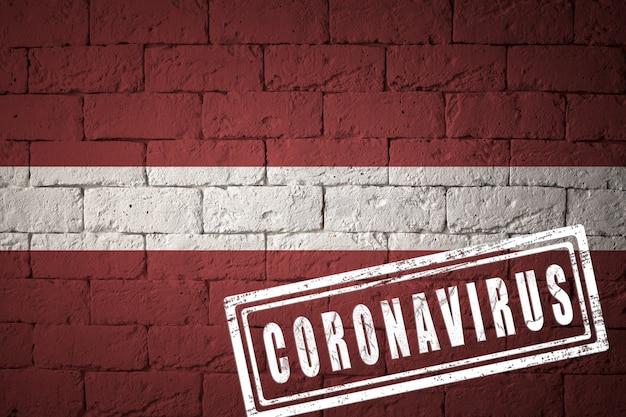 Flaga łotwy o oryginalnych proporcjach. opieczętowane koronawirusem. cegła ściana tekstur. koncepcja wirusa koronowego. na skraju pandemii covid-19 lub 2019-ncov.