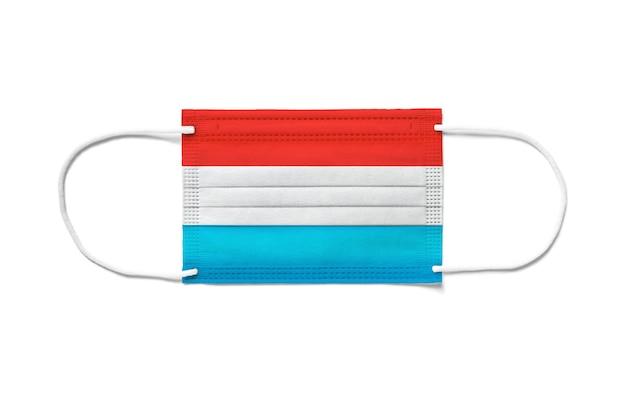 Flaga luksemburga na jednorazowej masce chirurgicznej. białe tło na białym tle