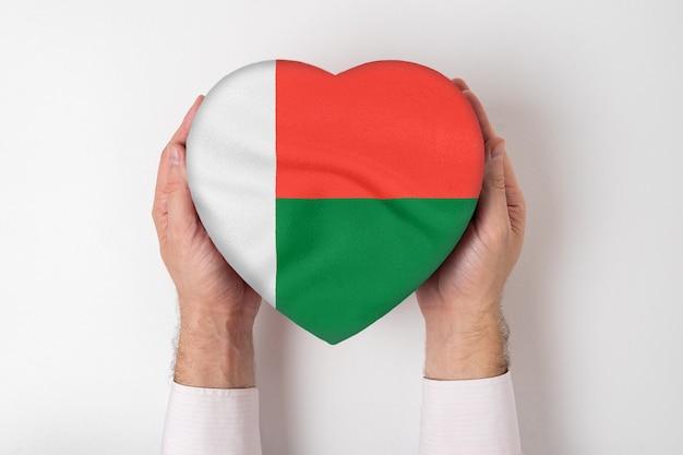 Flaga madagaskaru na pudełku w kształcie serca w męskich rękach. białe tło