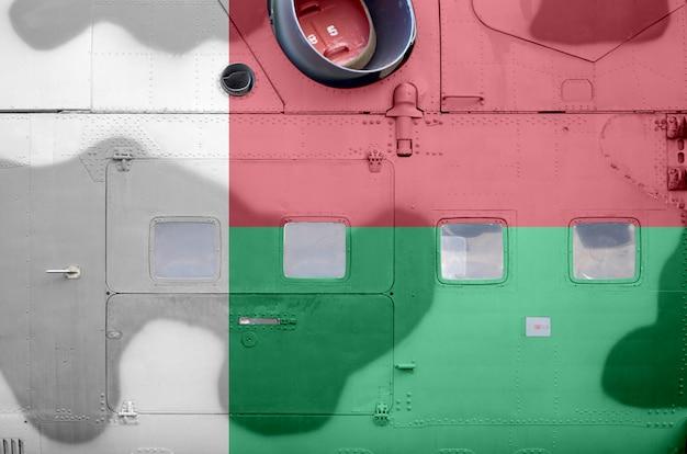 Flaga madagaskaru przedstawiona na bocznej części wojskowego helikoptera pancernego zbliżenie. armia sił samolotu koncepcyjne tło