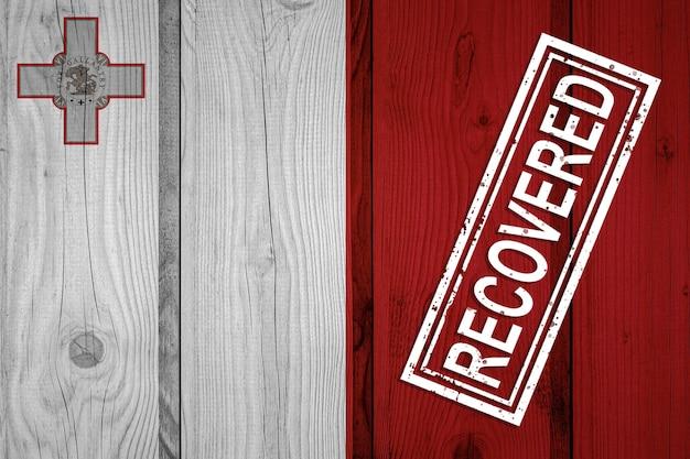 Flaga malty, która przeżyła lub wyzdrowiała z infekcji epidemii koronawirusa lub koronawirusa. flaga grunge z pieczęcią odzyskane
