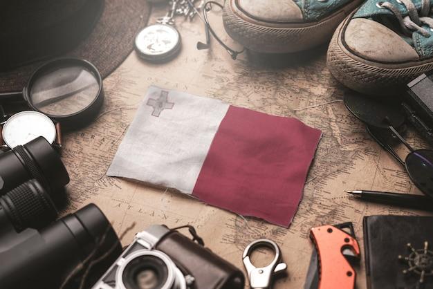 Flaga malty między akcesoriami podróżnika na starej mapie vintage. koncepcja miejsca turystycznego.