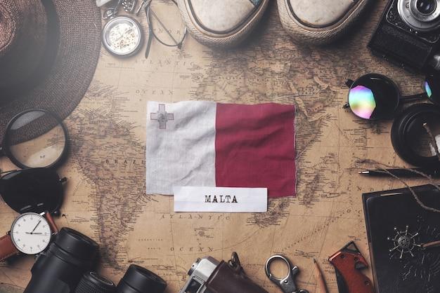 Flaga malty między akcesoriami podróżnika na starej mapie vintage. strzał z góry