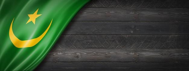 Flaga mauretanii na czarnej ścianie z drewna. poziomy baner panoramiczny.