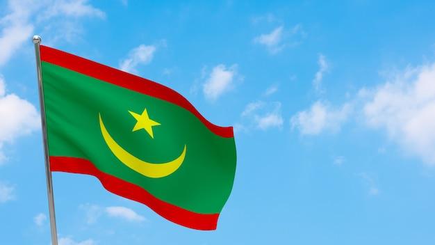 Flaga mauretanii na słupie. niebieskie niebo. flaga narodowa mauretanii