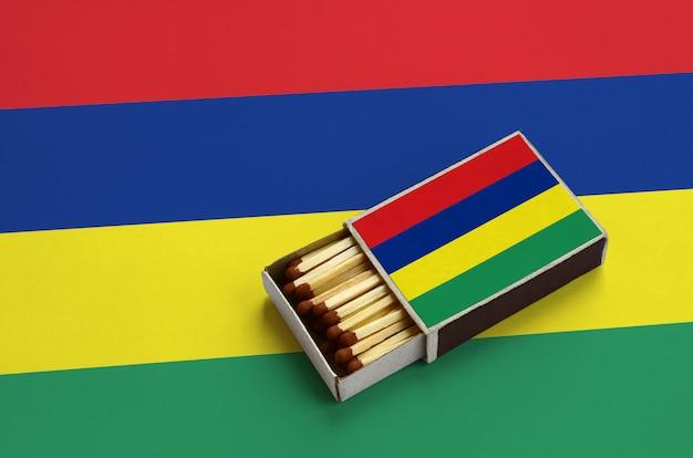 Flaga mauritiusa jest pokazana w otwartym pudełku zapałek, które jest wypełnione zapałkami i leży na dużej fladze