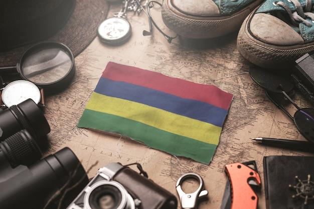 Flaga mauritiusa między akcesoriami podróżnika na starej mapie vintage. koncepcja miejsca turystycznego.