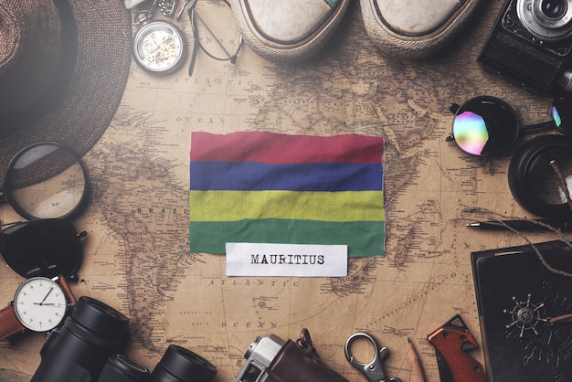 Flaga mauritiusa między akcesoriami podróżnika na starej mapie vintage. strzał z góry