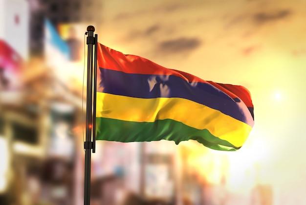 Flaga mauritiusa przeciw miastu zamazane tło w sunrise backlight