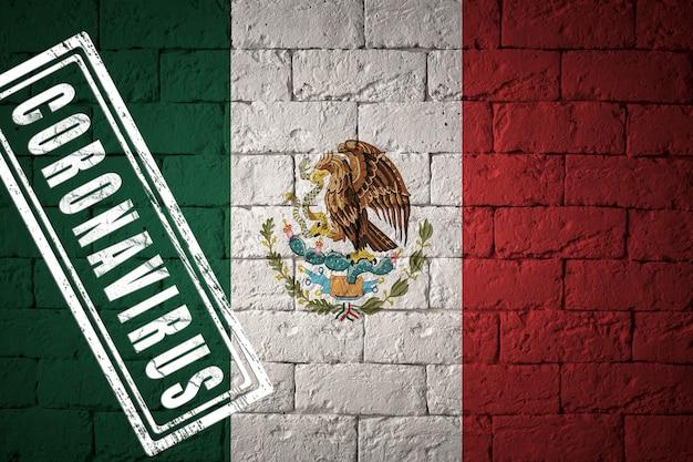 Flaga meksyku o oryginalnych proporcjach. opieczętowane koronawirusem. cegła ściana tekstur. koncepcja wirusa koronowego. na skraju pandemii covid-19 lub 2019-ncov.