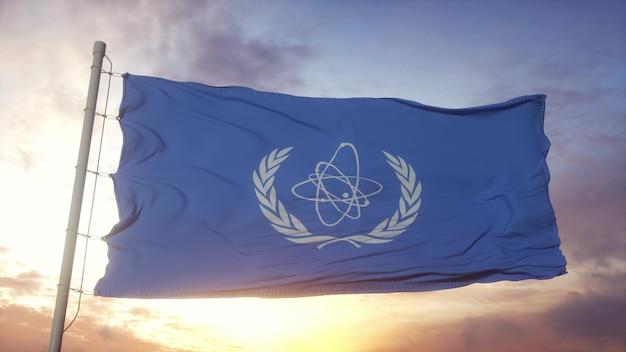 Flaga międzynarodowej agencji energii atomowej maea macha na tle wiatru, nieba i słońca. renderowanie 3d