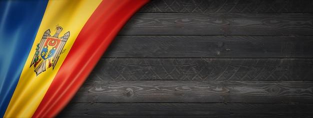 Flaga mołdawii na czarnej ścianie z drewna. poziomy baner panoramiczny.