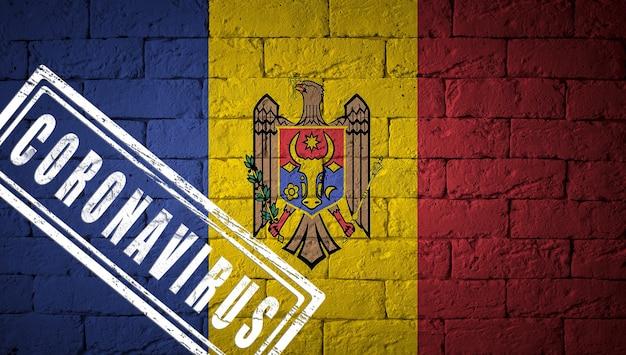 Flaga mołdawii o oryginalnych proporcjach. opieczętowane koronawirusem. cegła ściana tekstur. koncepcja wirusa koronowego. na skraju pandemii covid-19 lub 2019-ncov.